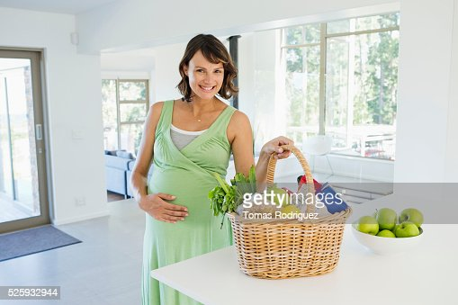 Pregnant woman holding basket with vegetables in kitchen : Stockfoto