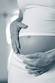 Pregnant woman holding belly.