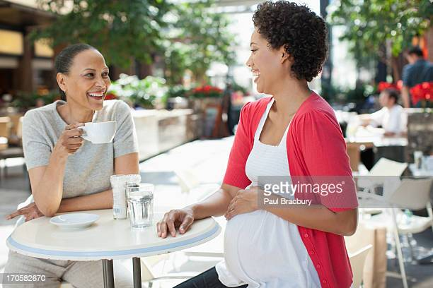 Pregnant woman holding stomach at cafe with friend