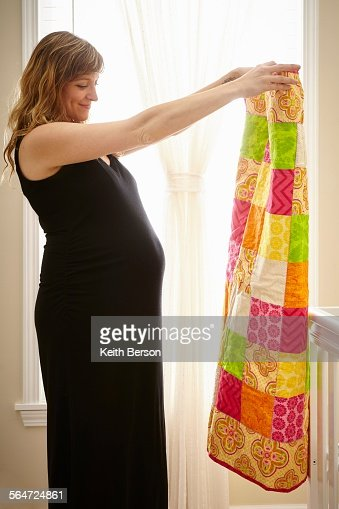 Pregnant woman holding up homemade quilt in nursery