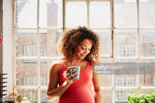 A pregnant woman holds a coffee cup whilst smiling