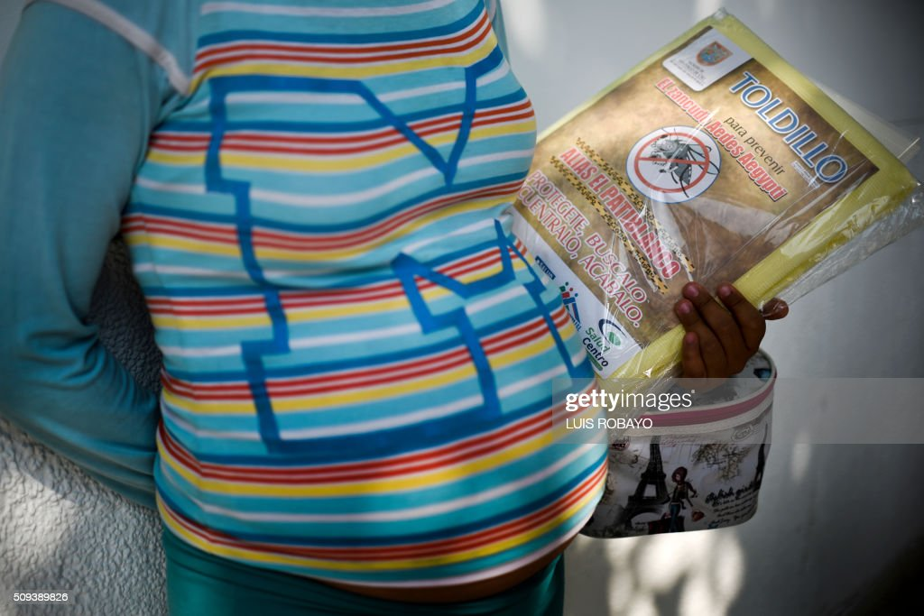 A pregnant woman holds a mosquito net in Cali on February 10, 2016. The Colombian Health Ministry began delivering mosquito nets for free to pregnant women to prevent the infection by Zika virus, vectored by the Aedes aegypti mosquito. The World Health Organization on Tuesday urged caution about linking the Zika virus with a rare nerve disorder called Guillain-Barre which health officials in Colombia have blamed for three deaths. AFP PHOTO / LUIS ROBAYO / AFP / LUIS ROBAYO