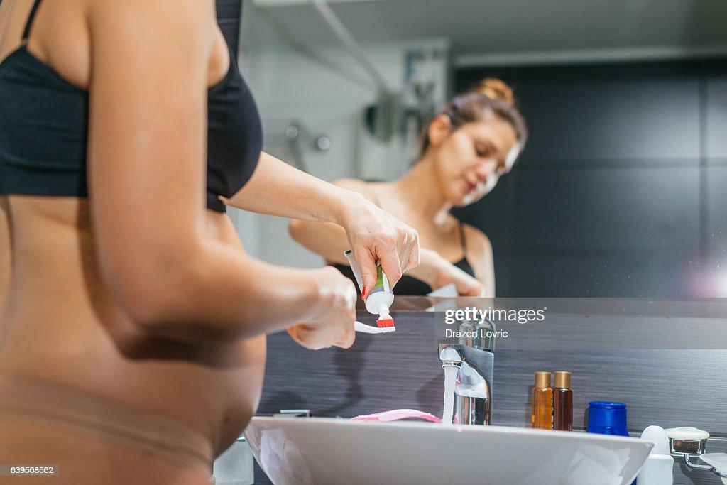 Pregnant woman in bathroom brushing her teeth : Stock Photo
