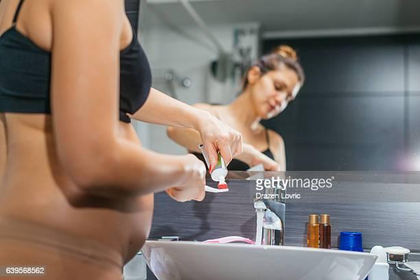 Pregnant woman in bathroom brushing her teeth