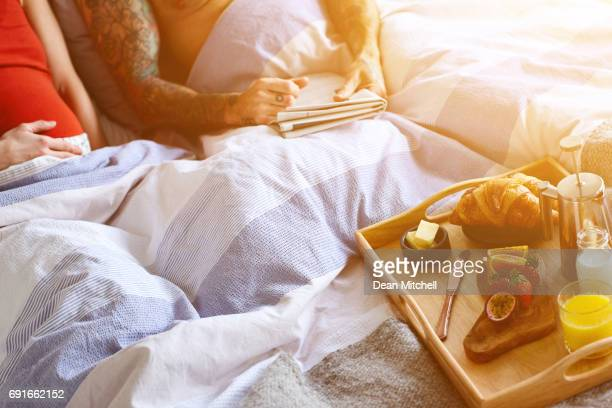 Pregnant woman in bed with breakfast and newspaper