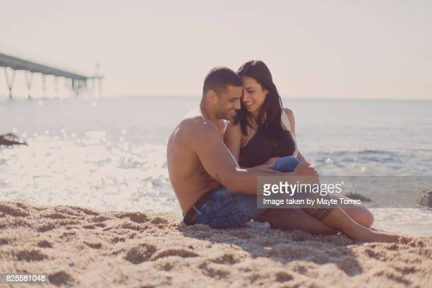 Pregnant woman in bikini at the beach with partner laughing and looking at him