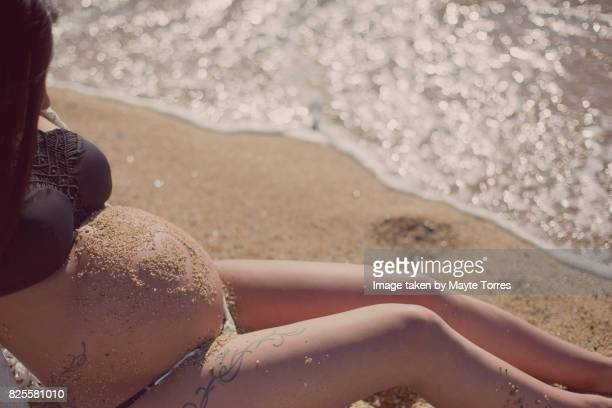 Pregnant woman in bikini with a sand heart in her belly