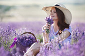Cute smiling pregnant woman resting in a lavender field. Posing outdoors. Motherhood. Motherhood.Lavender field and a happy pregnant woman.Young beautiful pregnant woman in a hat from the sun on summe