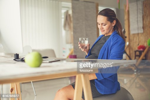 Pregnant woman in office drinking water : Stock Photo