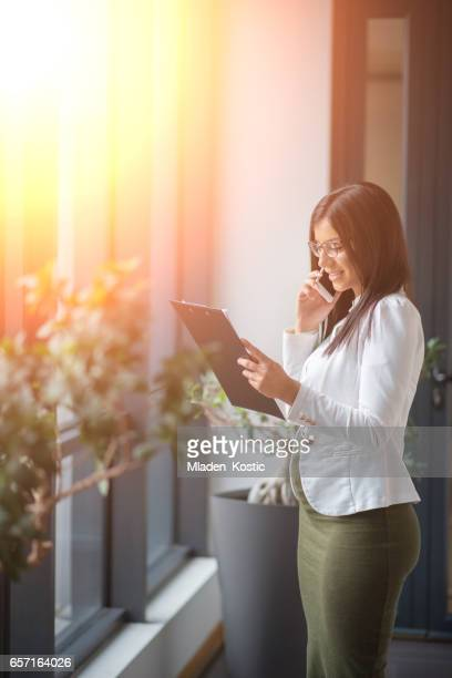 Pregnant woman in office talking on phone