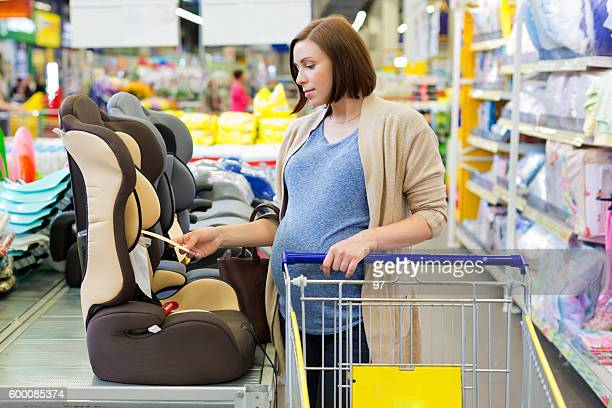 pregnant woman in shop buy car baby seat