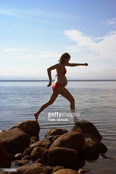 Pregnant woman in swimsuit jumping on rocks by sea