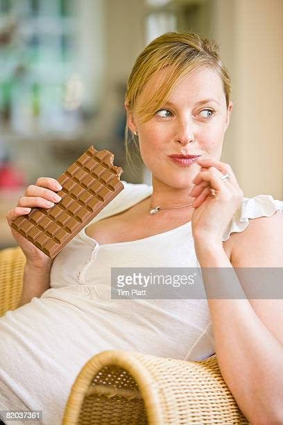 Pregnant woman, late twenties, eating a bar of chocolate.