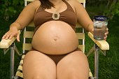 Pregnant woman laying in lawn chair wearing bathing suit