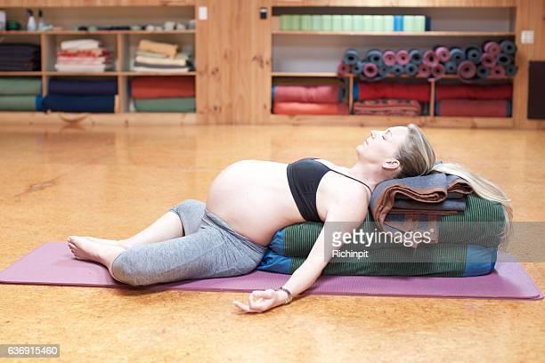 Pregnant woman lies in savasana yoga pose