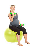 Pregnant woman lifting weights on exercise ball