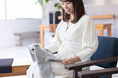 Pregnant woman looking at children's clothes