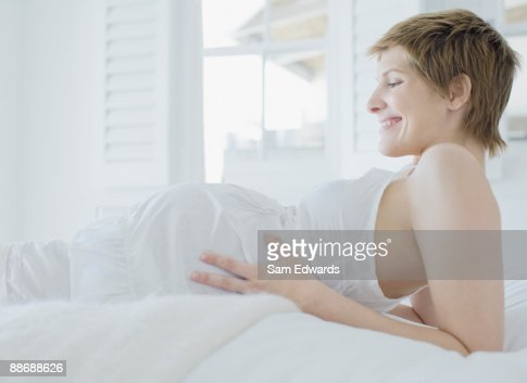 Pregnant woman looking at stomach : Stock Photo