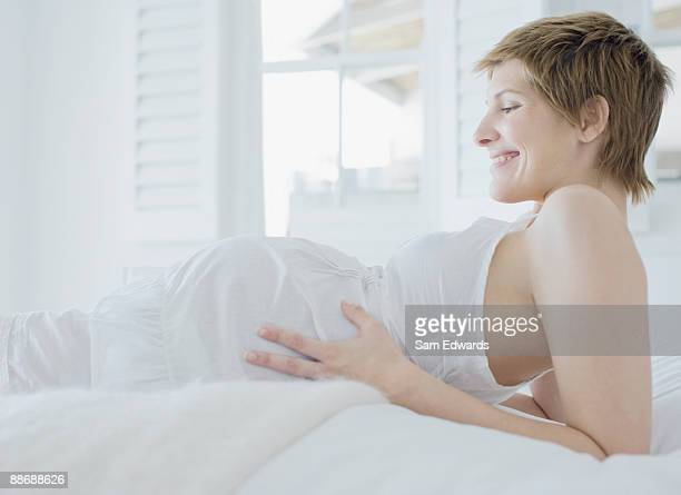 Pregnant woman looking at stomach