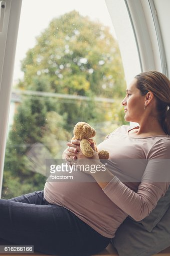 Pregnant woman looking out the window : Stock Photo
