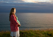 Pregnant woman looking out to sea.