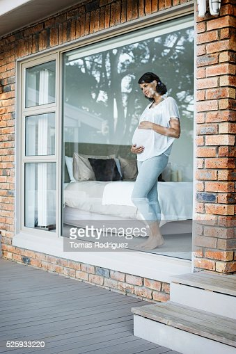 Pregnant woman looking through window : Stock Photo