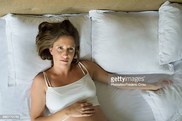 Pregnant woman lying in bed alone