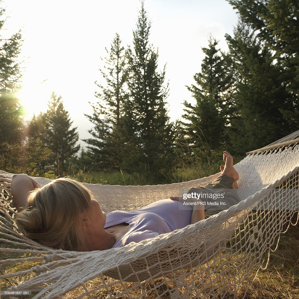 Pregnant woman lying in hammock, rear view, sunset : Stock Photo