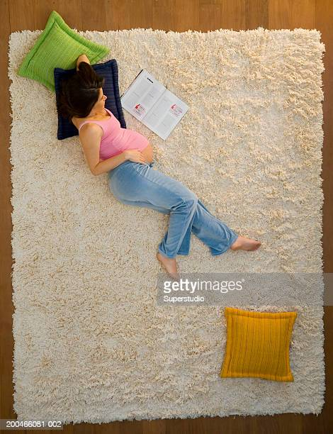 Pregnant woman lying on floor, reading, elevated view