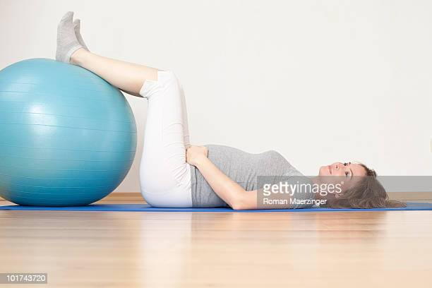 Pregnant woman lying and exercising with fitness ball