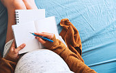 Pregnant woman makes notes and looking at medical documents. Concept of pregnancy, health care, gynecology, medicine. Mother waiting of baby.