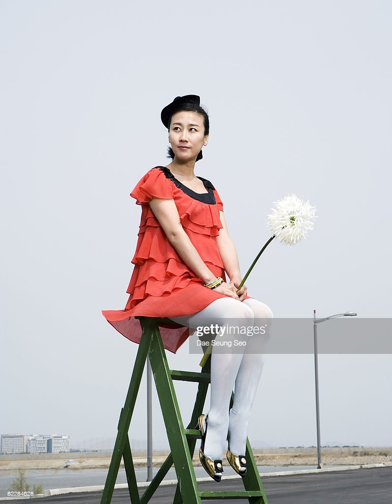 Pregnant woman on ladder with flower : Stockfoto