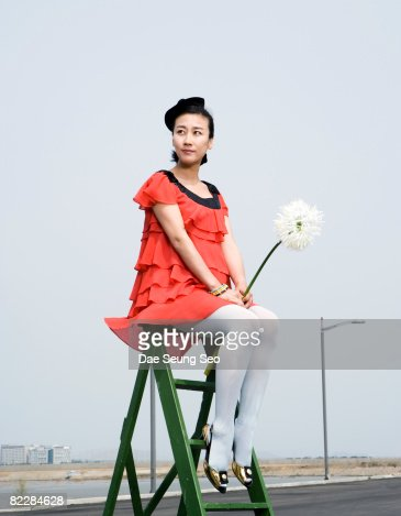 Pregnant woman on ladder with flower : Stock-Foto