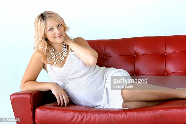 Pregnant woman on red sofa
