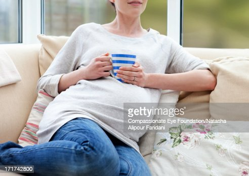 Pregnant woman on sofa holding mug : Stock Photo