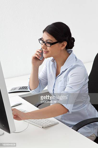 Pregnant woman on the phone in office