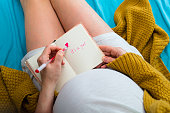 Pregnant woman writing in notebook. Aerial close up view.