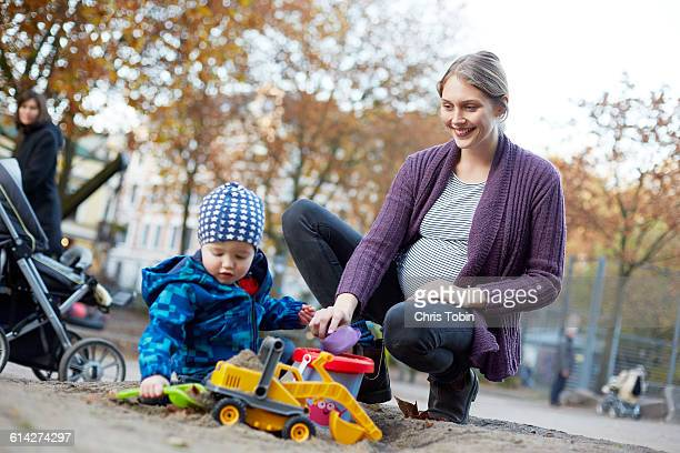 Pregnant woman playing with toddler on playground