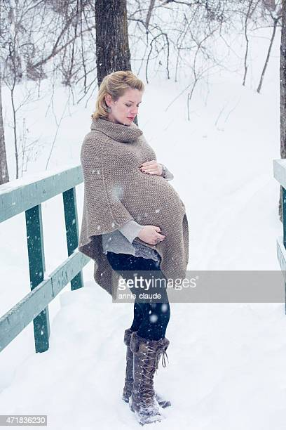 Pregnant woman posign in a snowy landscape