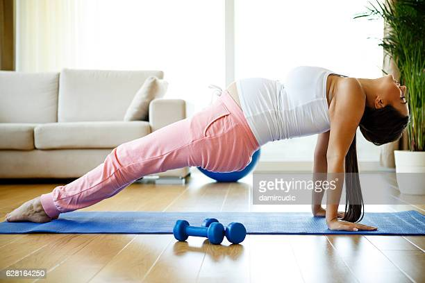 Pregnant woman practicing yoga and fittness at home