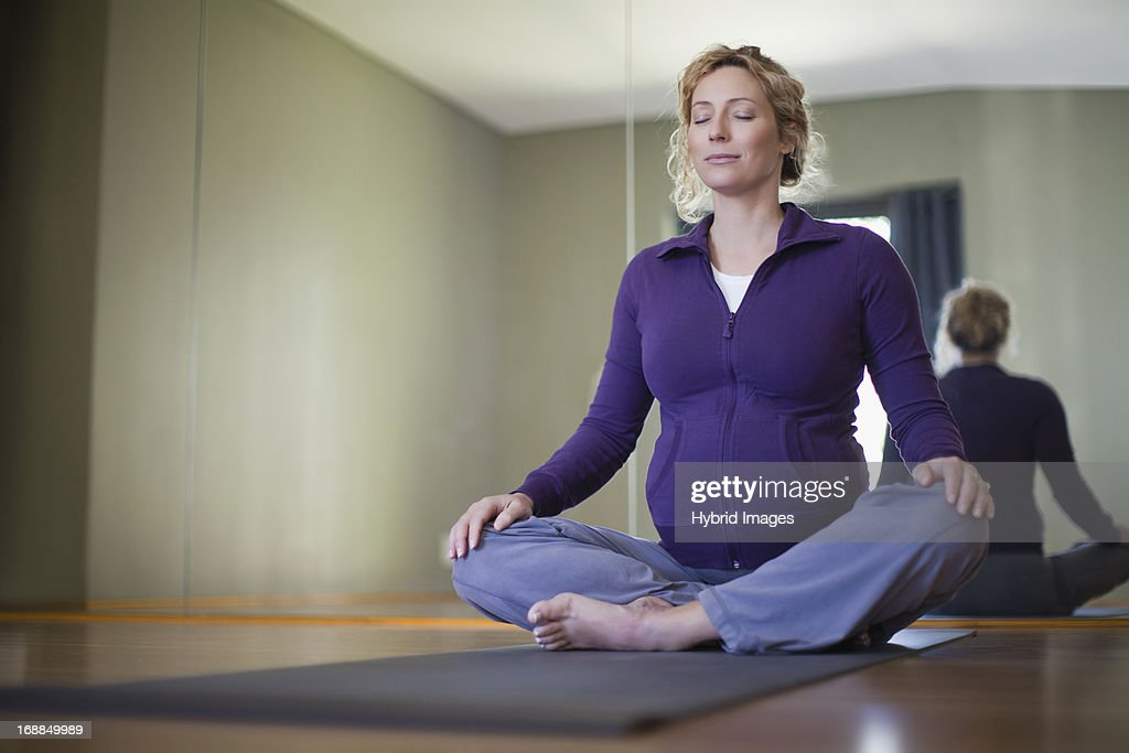 Pregnant woman practicing yoga in studio