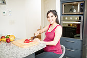 Smiling mid adult woman slicing apple on cutting board during her pregnancy in kitchen at home