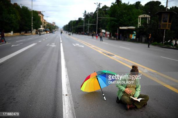 A pregnant woman reads a book as she sits on an empty boulevard in central Sofia on the sidelines of massive antigovernment protests on June 27 to...