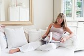 Pregnant woman reclining on sofa with book