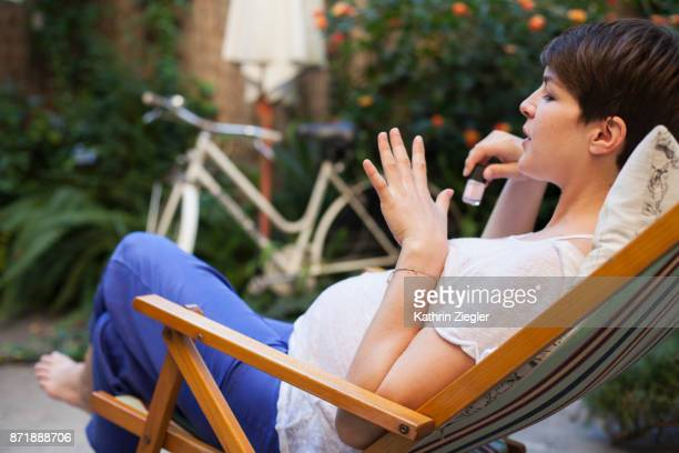 Pregnant woman relaxing on deck chair, doing her nails