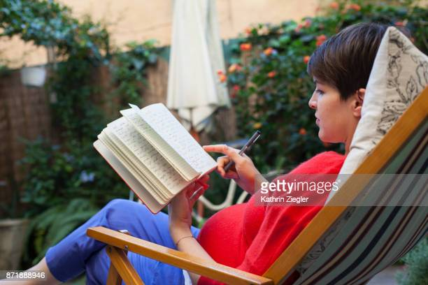 Pregnant woman relaxing on deck chair, flipping through journal