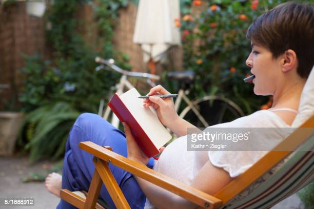 Pregnant woman relaxing on deck chair, writing in journal