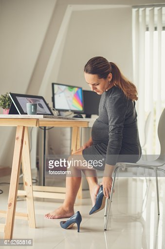 Pregnant woman removing shoes : Stock Photo