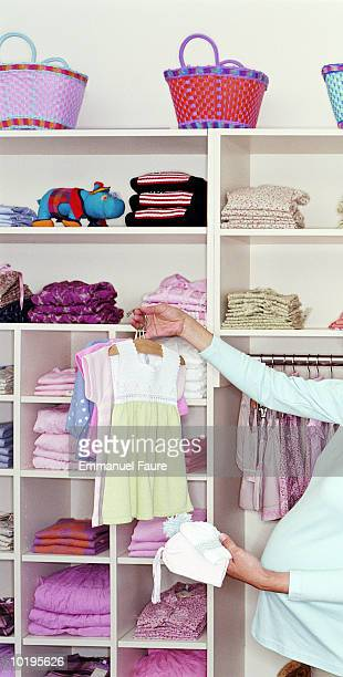 Pregnant woman shopping for baby clothes, mid section