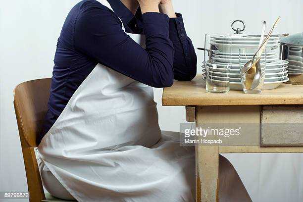 A pregnant woman sitting a table stacked with dishes